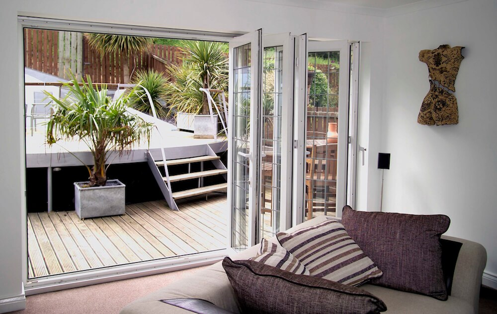 Bi-fold doors opening up a living room to a back garden